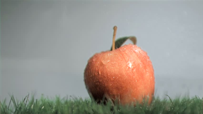 Red apple in super slow motion getting wet against a grey background