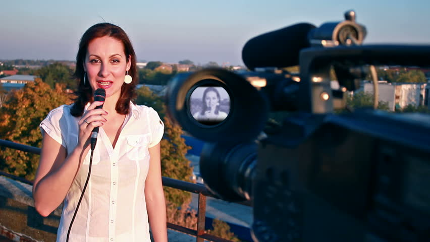 TV reporter on assignment ; TV reporter in front of the camera gives notice of the weather forecast at the top of the building
