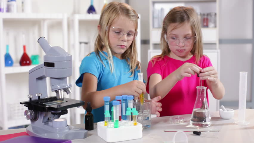 Little girls enjoy working with different liquid while learning about chemistry.