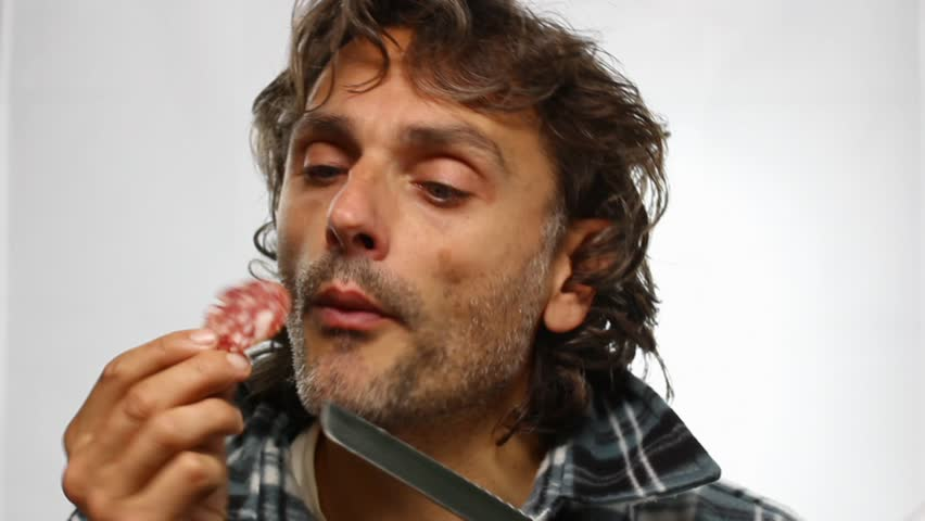 funny unshaven man eating salami - HD stock video clip