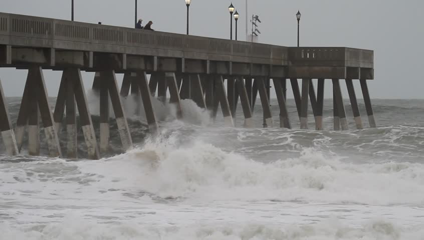 Wide Shot of Atlantic Ocean Waves Crash into Johnny Mercer Pier at Wrightsville Beach North Carolina as Hurricane Sandy Passes Along the Coast.  Waves spray up as they hit the pilings of the pier.