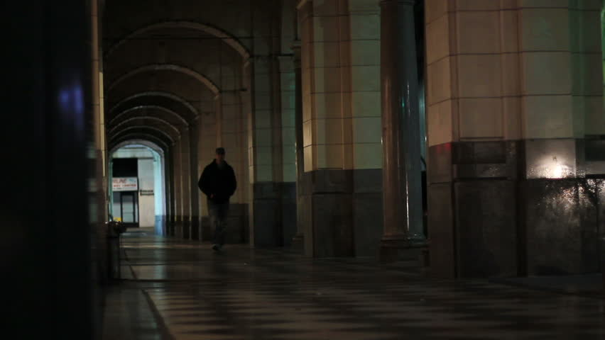 A man walks down a dark arched pathway at night alone