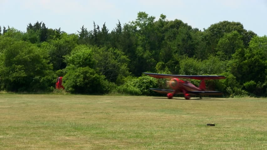 Red biplane takes off at Cape Cod Airfield taking passengers on tour of Cape Cod