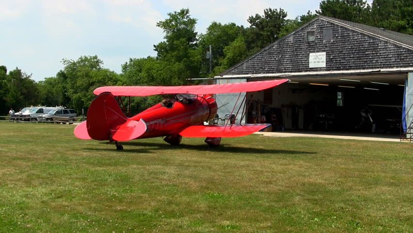 CAPE COD AIRFIELD, MARSTON MILLS,  MA. - JULY 13th; Engine fires up on red biplane to take passengers on aerial tour of cape cod and islands July 13th, 2012 Marston Mills, MA.