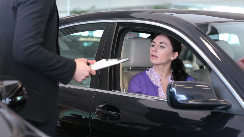 Woman signing on a notepad in a car
