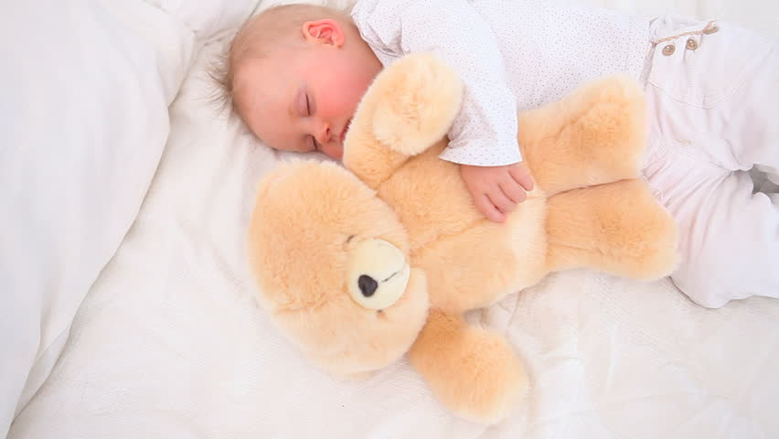 Baby sleeping with a teddy bear in a bedroom