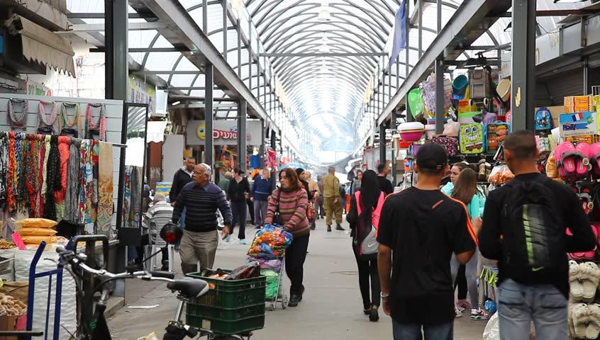 RAMLE, ISRAEL - NOVEMBER 27: Shoppers buy produce and clothing at Ramlod Market, Ramla, Israel on November 27, 2012