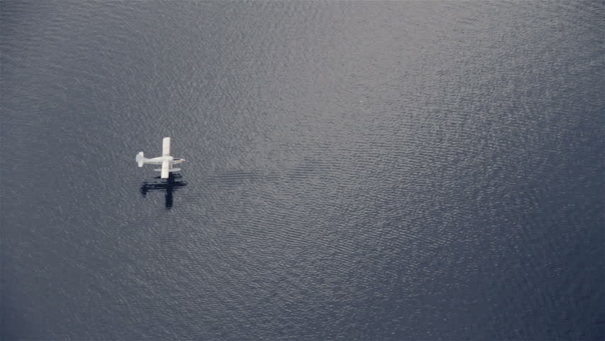 View from airplane of float plane on lake water approaching and landing - HD stock video clip