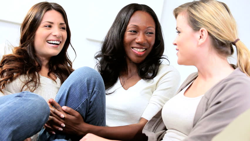 Multi ethnic women laughing and gossiping on comfortable couch - HD stock video clip
