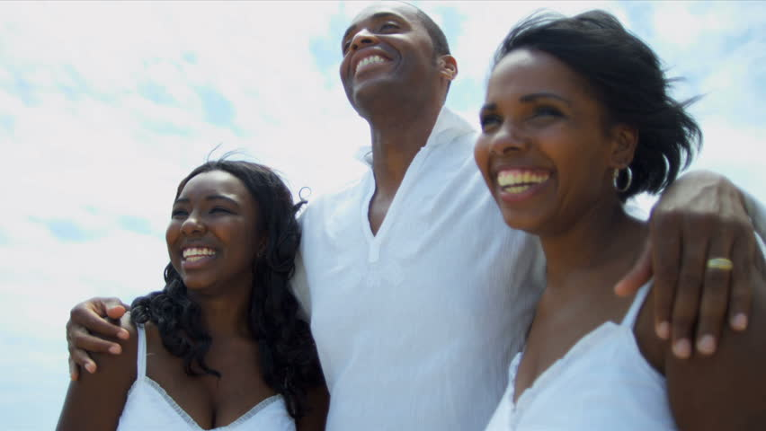 African American family spending together time on beach all dressed in white