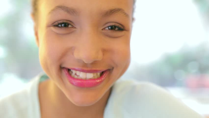 Close up portrait of a young child girl smiling at the camera. Out of focus image clears into focus as the girl smiles.