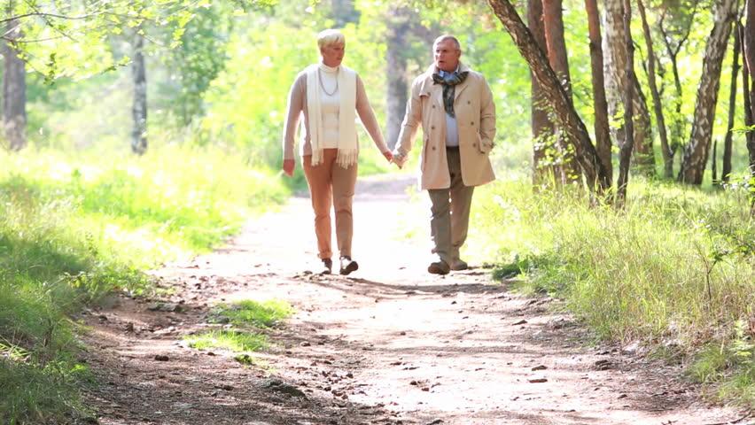 Charming seniors taking an unhurried walk in late summer