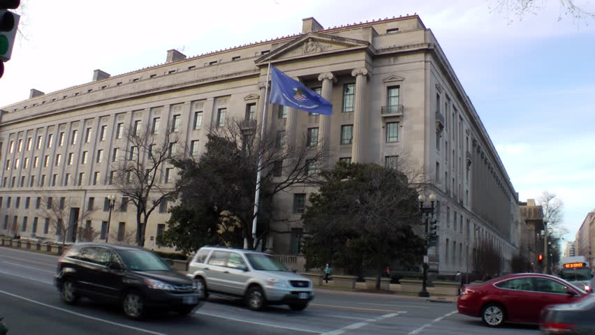Headquarters of the U.S. Justice Department in Washington, DC.  Renamed Robert F. Kennedy Department of Justice Building in 2001. No recognizable pedestrians.  Blue flag is the Dept. of Justice flag.