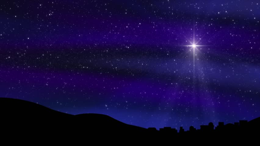 Seamless loop features the Bethlehem Christmas Nativity star with hundreds of twinkling stars in a colorful night sky silhouetting the town of Bethlehem. Light rays and sparkling particles.