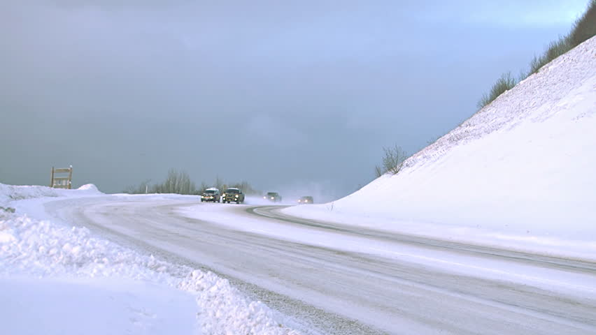 HOMER, AK - CIRCA 2012: Several vehicles being driven on a snowy Alaskan road in the winter time. - HD stock footage clip