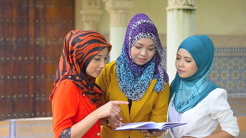 Three young pretty Asian muslim business woman in head scarf with book  - HD stock video clip
