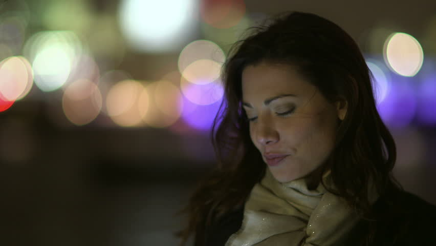 A beautiful young professional woman is having a phone conversation, outdoors in the city at night. She is smiling and the bright lights of the big city can be seen in the background behind her.