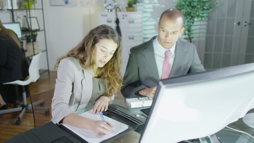 Office or security workers sitting and working together in front of their computers. Another worker can be seen in the background with a whole bank of computer monitors in front of her. Slow motion - HD stock footage clip