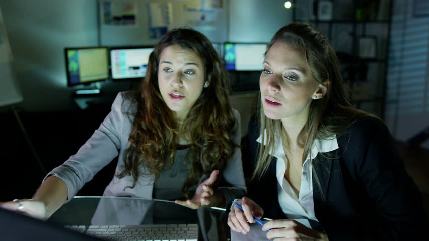 2 attractive female office workers are working late at night, a bank of computer screens can be seen in the background. Slow motion.