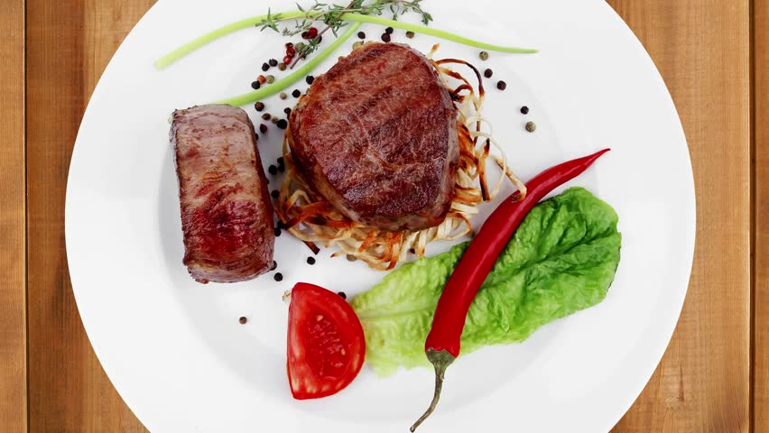 grilled beef fillet with thyme red hot chili pepper and tomato on plate  over wooden table