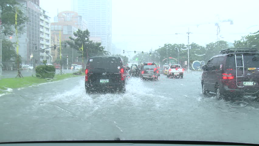 MANILA, PHILIPPINES - CIRCA AUGUST 2012: Driving In Flooded Road Tropical Storm. Cars and vehicles struggle to drive through flooded streets during torrential rainstorm.