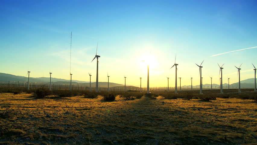 Wind turbines producing clean alternative energy in silhouette at sunset - HD stock video clip