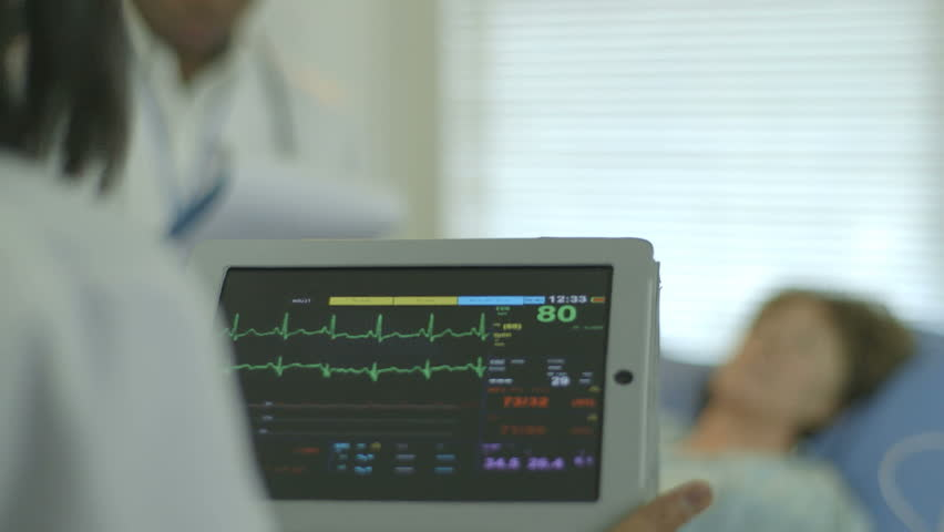 A doctor or nurse in a hospital setting looks at the vitals and other data being displayed on a portable patient monitor she is holding. - HD stock footage clip