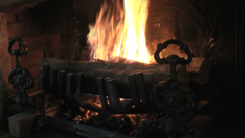 Man positions logs in burning fireplace. 1080p - HD stock video clip