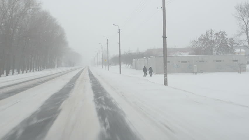 car go on road near small town and snowstorm snow falling. people walk. front car window view. - HD stock footage clip