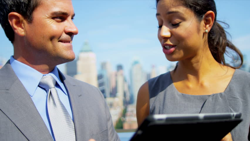 Close up of smart multi ethnic business managers using touch screen technology on rooftop overlooking city shot on RED EPIC