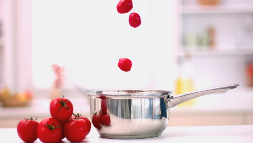 Cherry tomatoes falling in pot in kitchen in slow motion