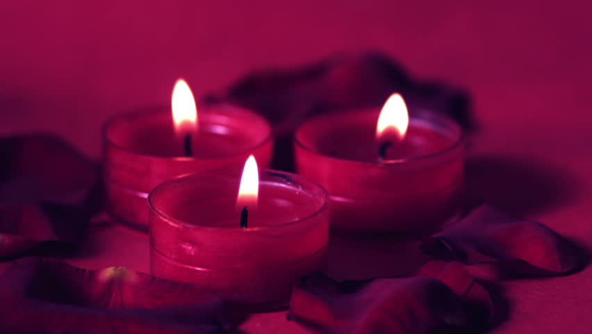 pink candles flickering surrounded by rose petals in slow