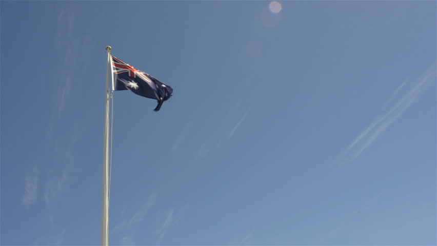 An Australian flag flying and flapping in the wind, with lots of blue sky. - HD stock footage clip