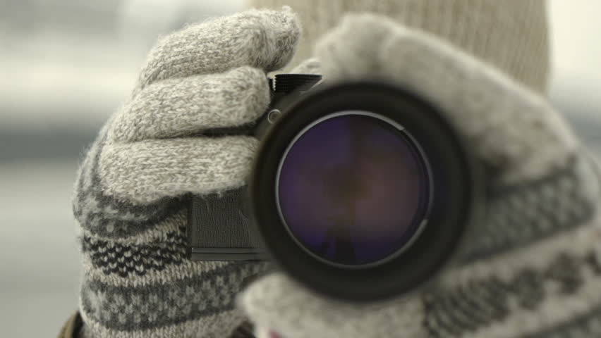 photographer operating aperture ring beautiful iris taking picture wearing worm gloves in winter time