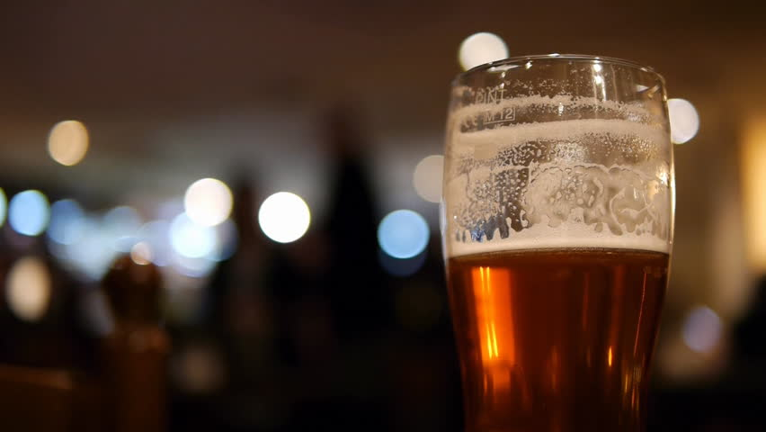 Beer Glass in a Pub. Half drunk glass of beer with an out of focus pub background.  - HD stock footage clip