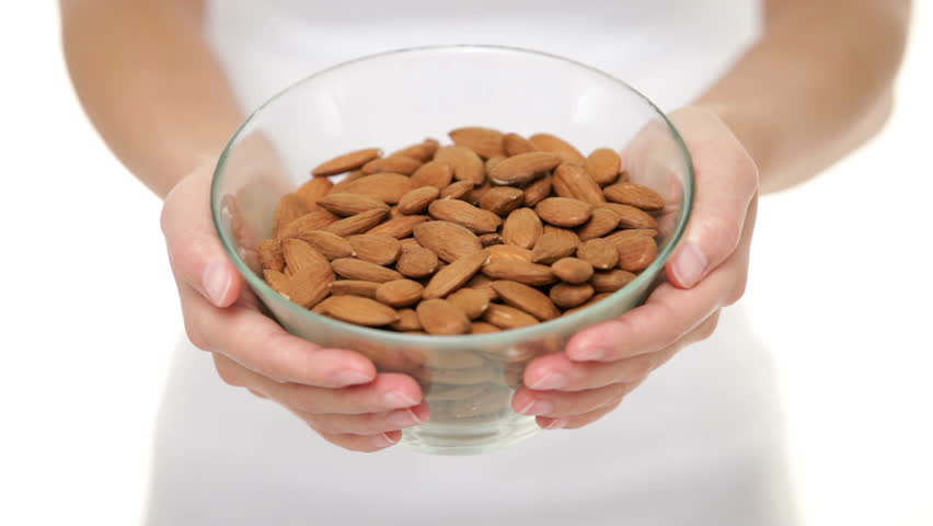 Almonds nuts - woman showing raw almond bowl closeup. Healthy food concept in studio with hands lifting bowl of unprocessed almonds up to focus on white background. - HD stock video clip