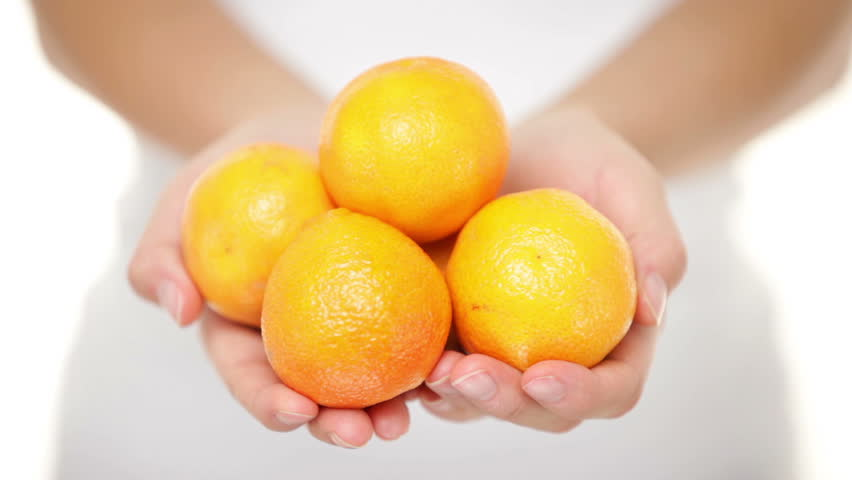 Clementine. Clementines that are a variety of mandarin oranges citrus fruits. Woman showing handful moving them into focus. Shot in studio with shallow depth of field.
