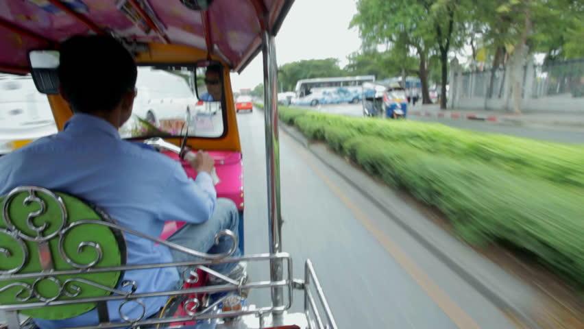 BANGKOK, THAILAND - MARCH 2011: Speeding auto rickshaw on busy streets on March 17, 2012 in Bangkok, Thailand. Auto rickshaws are the fastest ways of getting around congested Bangkok streets.