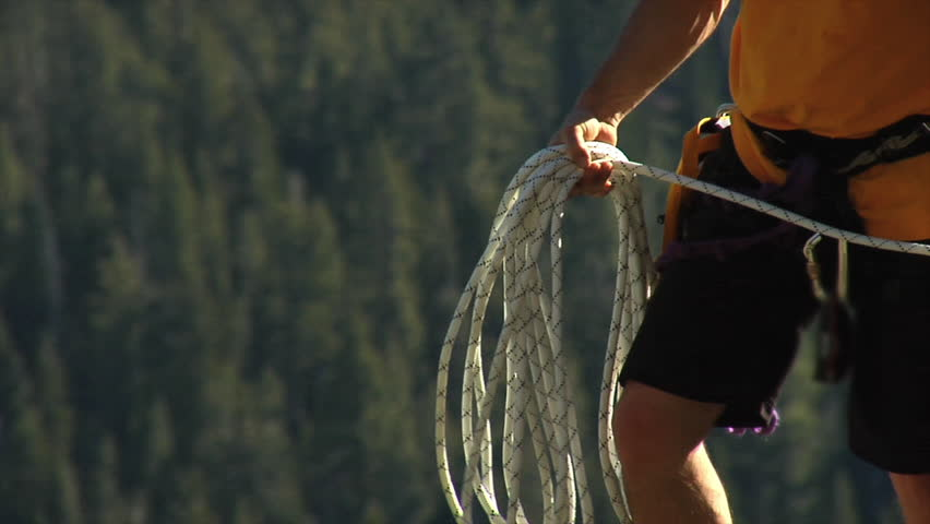 A male climber throws a safety rope across a gorge