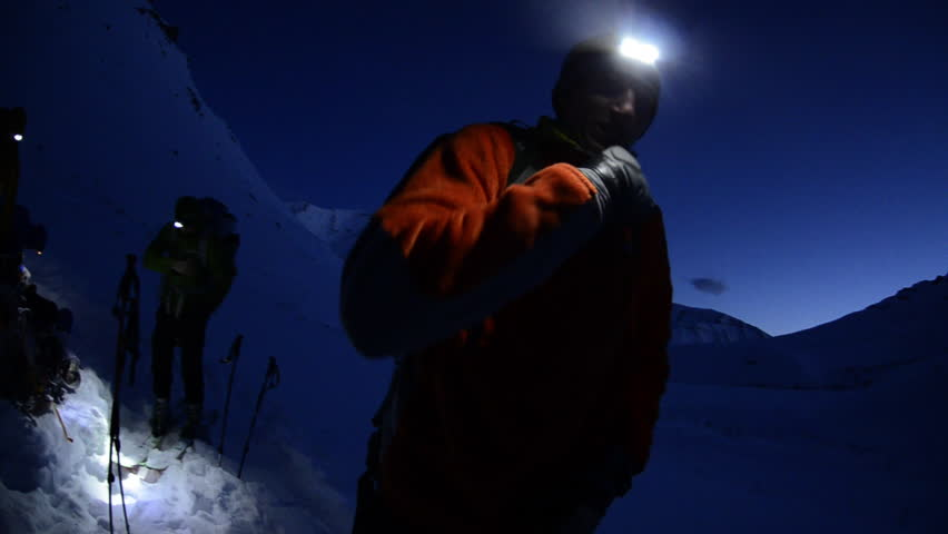 Hikers wake up before dawn and prepare to start their day of hiking in the dark in the snow covered Alaskan wilderness