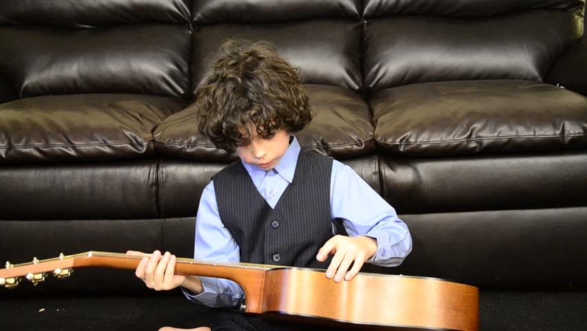 Young Hispanic boy trying to play guitar