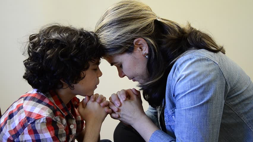 Hispanic mother and son praying together