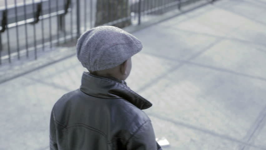 Young African American Kid walking down the street with a black coat and hat - HD stock video clip