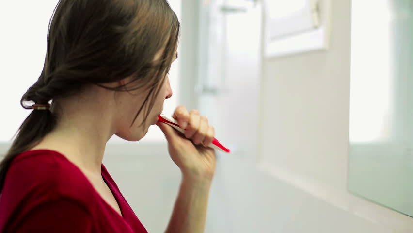 Young beautiful woman brushing teeth with a tooth brush in bathroom