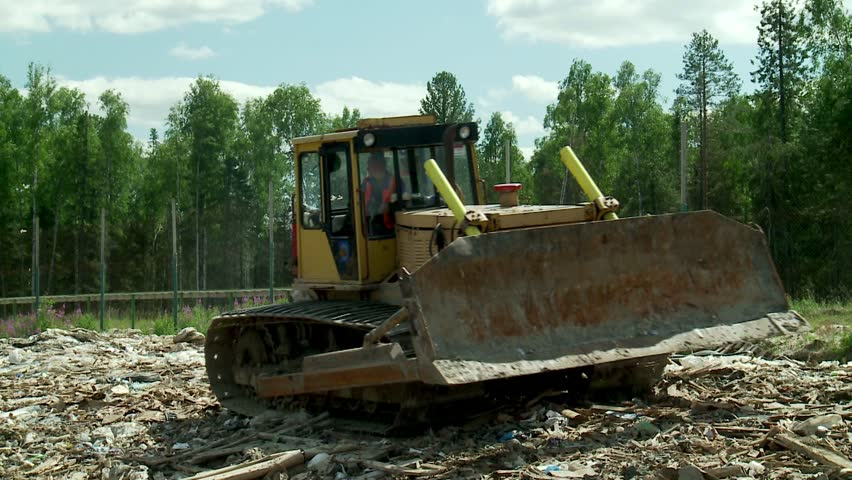 Landfills With Tractors : Tractor compacts the trash at a landfill stock footage
