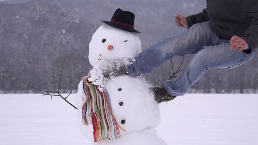 Man destroying a snowman slow motion