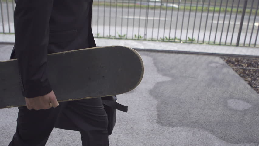 SLOW MOTION: Young businessman with skateboard - HD stock footage clip