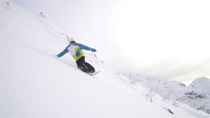 SLOW MOTION: snowboarder carving in fresh snow