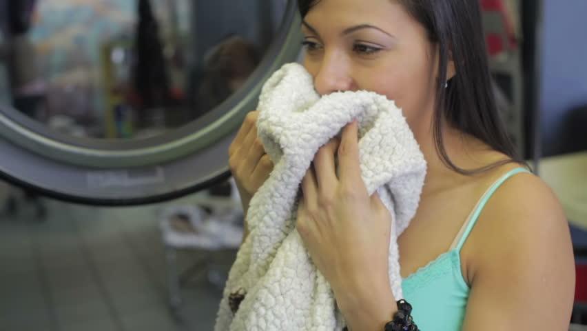 Beautiful woman smelling laundry