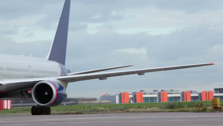 Worker pull ladder to aircraft with running turbines on airfield near airport terminal